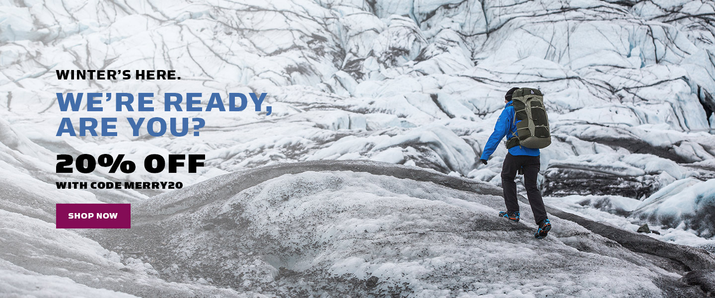 "Man in blue winter coat and backpack climbing a snowy mountain next to text that reads ""Winter's Here. 20% Off with code MERRY20."""